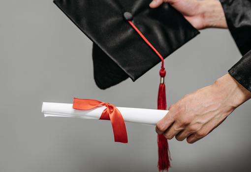 dyplom i birret w dłoniach